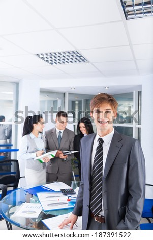 handsome young businessman happy smile. at office with group of business colleagues people in the background businesspeople working in team at meeting - stock photo
