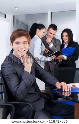 handsome young businessman happy smile. Sitting at the desk at office with group of business colleagues people in the background businesspeople working in team at meeting, man looking at camera - stock photo