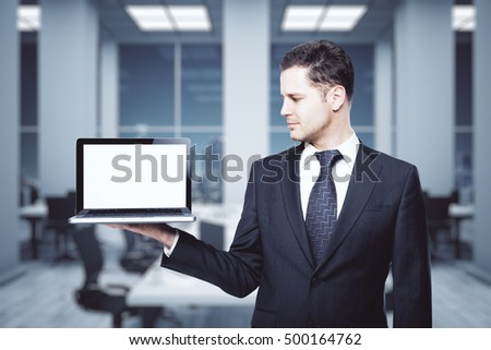 Handsome young businessman holding laptop computer with blank white screen. Presentation concept. 3D Rendering