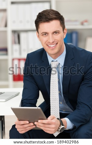 Handsome young businessman in a stylish suit sitting in his office holding a tablet computer in his hand and smiling at the camera - stock photo