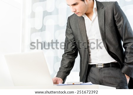 Handsome young businessman in a stylish suit standing at his desk checking his laptop computer for incoming information, over a high key background with copyspace. - stock photo