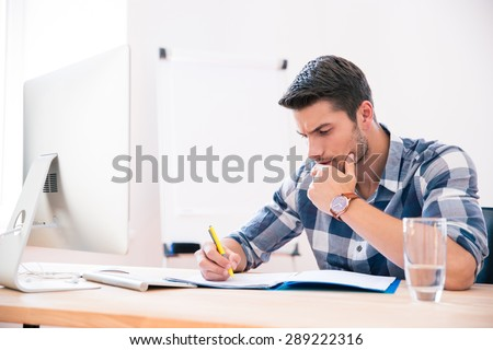 Handsome young businessman in casual cloth signing documents in office - stock photo