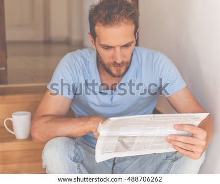 Handsome young businessman in casual clothes is reading a newspaper while sitting on stairs at home