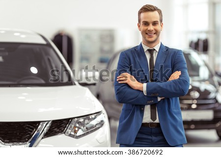 Handsome young businessman in classic blue suit is smiling and looking at camera while standing near the car in a motor show - stock photo