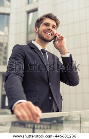 Handsome young businessman in classic suit is talking on the mobile phone and smiling, standing outside the office building - stock photo