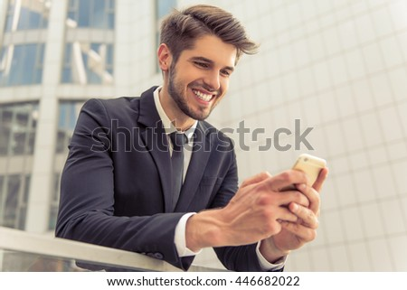 Handsome young businessman in classic suit is using a smartphone and smiling, standing outside the office building