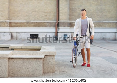 Handsome young businessman is walking on the city street with his bicycle beside him. He is looking at camera and smiling. - stock photo