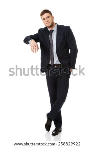 Handsome young businessman leaning on copy space. - stock photo