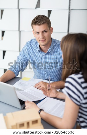 Handsome Young Businessman Listening to his Female Colleague Talking While Having a One on One Meeting Inside the Office. - stock photo