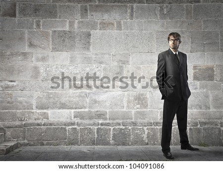 Handsome young businessman on a city street - stock photo