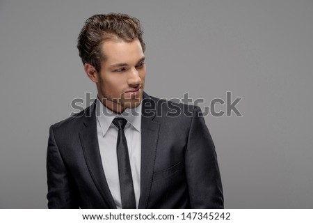 Handsome young businessman. Portrait of handsome young businessmen looking away while standing isolated on grey - stock photo