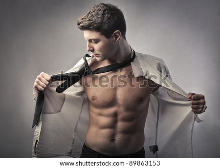 Handsome young businessman putting on his skirt and tie - stock photo