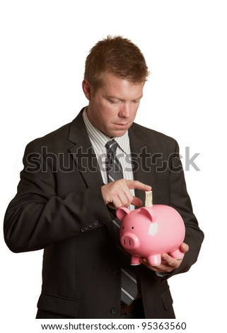 Handsome young businessman saving money in piggy bank isolated - stock photo