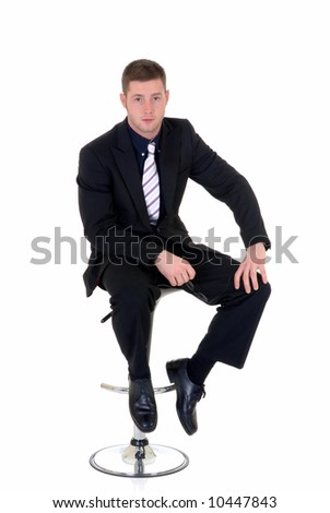 Handsome young businessman, sitting on bar stool, troubled pensive look, studio shot.