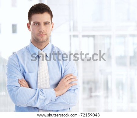 Handsome young businessman standing arms crossed.?