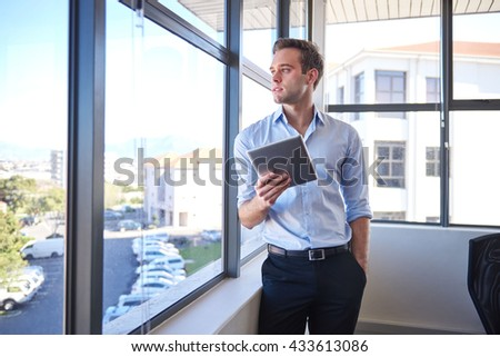 Handsome young businessman, standing in his office with his hand in his pocket and holding a digital tablet, while looking out of his office window and thinking - stock photo