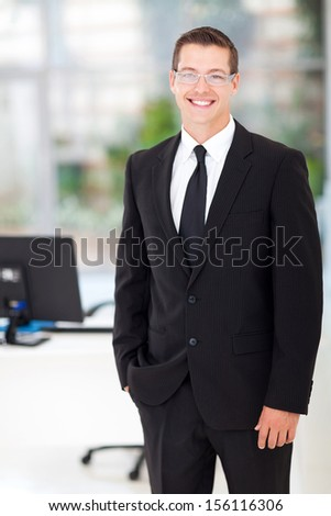 handsome young businessman standing in office - stock photo