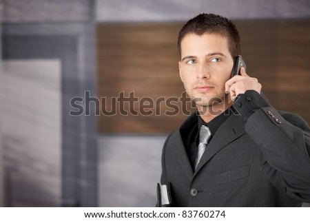 Handsome young businessman talking on mobile phone.?