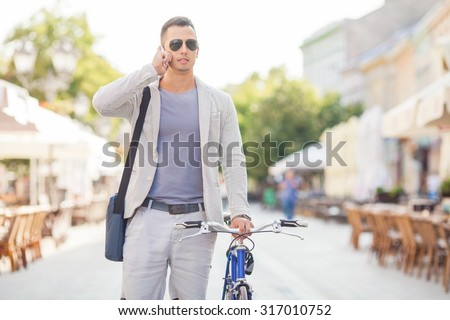 Handsome young businessman talking on the phone and walking down the city street with his bicycle beside him - stock photo