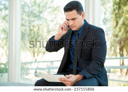 Handsome young businessman talking over the phone with his cell phone while using a tablet computer - stock photo