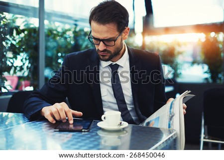 Handsome young businessman use digital tablet pressing the button and locked to the screen, business man reading news during his breakfast - stock photo