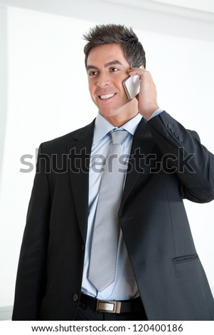Handsome young businessman using cellphone at workplace - stock photo