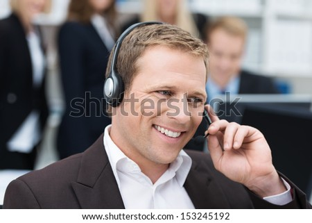 Handsome young businessman with a warm smile taking a call on a headset as he deals with queries at the customer support call centre - stock photo