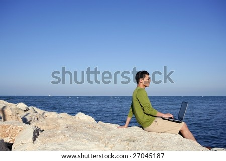 Handsome young businessman with computer on the blue ocean beach - stock photo