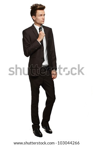 Handsome young businessman with pen in hand   with a slight smile on his face