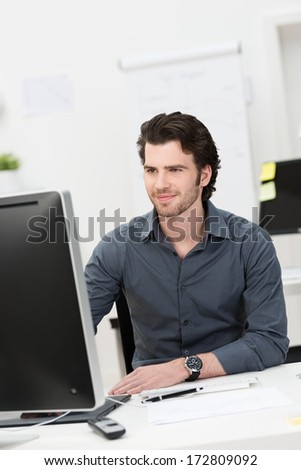 Handsome young businessman working at his desktop computer sitting at his desk in the office - stock photo