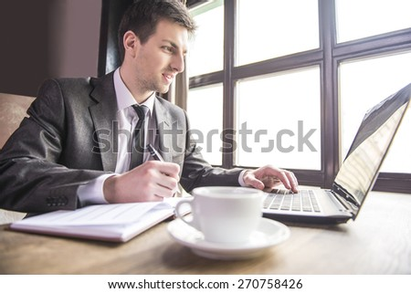 Handsome young businessman working at laptop and notebook in restaurant.