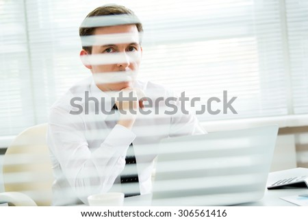 Handsome young businessman working at laptop in office. View through blinds
