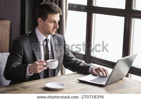 Handsome young businessman working at laptop with cup of coffee in restaurant.