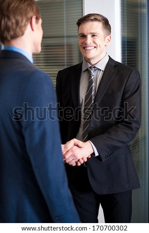 Handsome young businessmen shaking hands - stock photo
