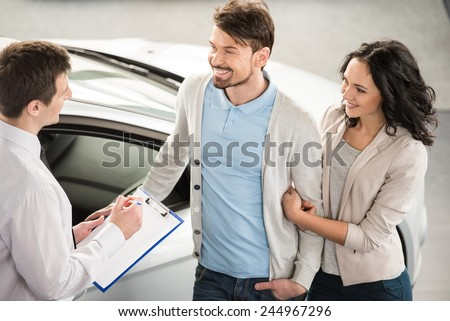 Handsome young car salesman isnstanding at the dealership telling about the features of the car to the couple. - stock photo
