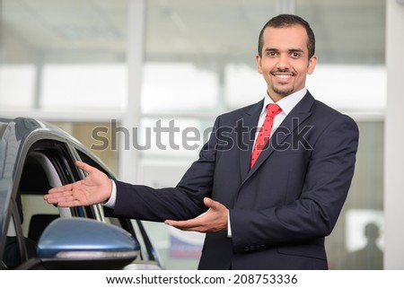 Handsome young car salesman standing at the dealership and pointing car - stock photo