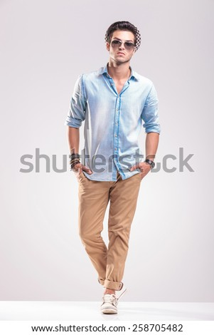 Handsome young casual man posing on grey background with both hands in his pocket. - stock photo
