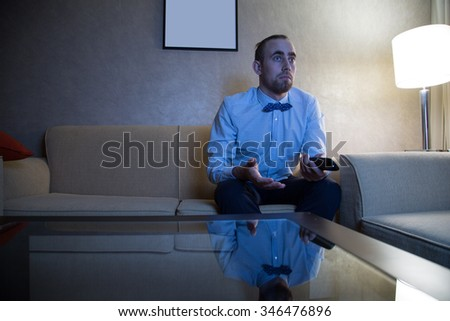 Handsome young caucasian man in a blue shirt and bow tie watching TV frustrated