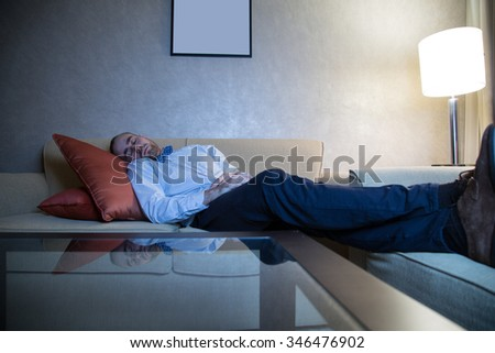 Handsome young caucasian man in a blue shirt and bow tie watching TV sleeping