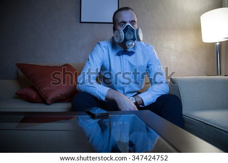 Handsome young caucasian man in a blue shirt and respirator watching TV