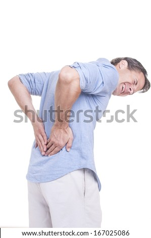 Handsome young Caucasian man in blue shirt struggles with intense back pain on white background