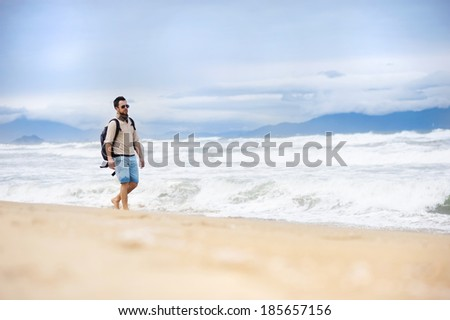 Handsome young Caucasian man walking alone with backpack on the beach - stock photo