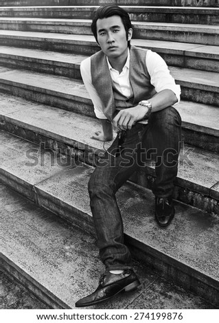 Handsome young Chinese man sitting on old concrete stairs, holding sunglasses and looking at camera. Black and white image.  - stock photo