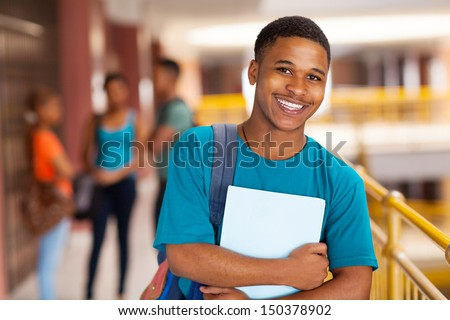 handsome young college boy holding books on campus - stock photo