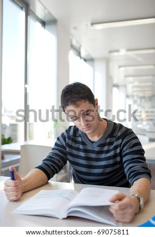 handsome young college student in a library (shallow DOF; color toned image) - stock photo