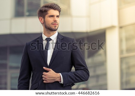 Handsome young confident businessman in classic suit is looking away, standing outside the office building