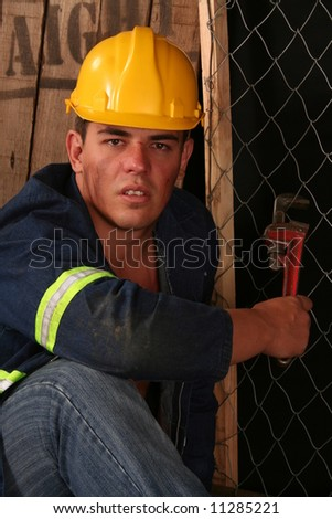 handsome young construction workman with safety helmet and spanner - stock photo