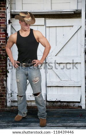 Handsome young country boy man wearing a stylish cowboy hat - stock photo