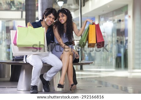Handsome young couple showing shopping bags at mall - stock photo