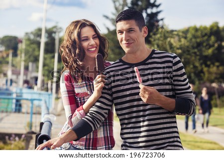 Handsome young couple walking together and licking ice cream - stock photo